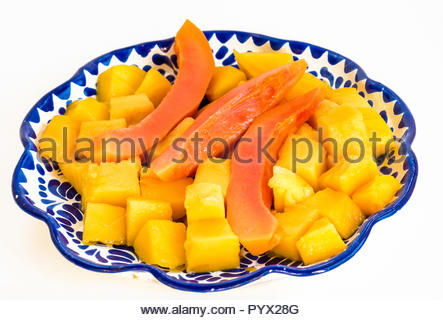 Healthy breakfast ideas: Diced mango pieces along with slices of ripe papaya in a serving plate, on a white background. - Stock Photo