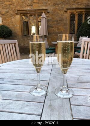 Two flutes of champagne sitting on wooden picnic table - Stock Photo