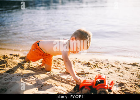 Caucasian child boy playing toy red tractor, excavator on a sandy beach by the river in red shorts at sunset day - Stock Photo