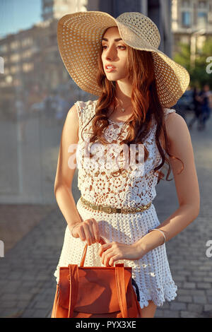 Close up portrait of a beautiful young woman near shop window during a sunny day. Lifestyle outdoors. - Stock Photo