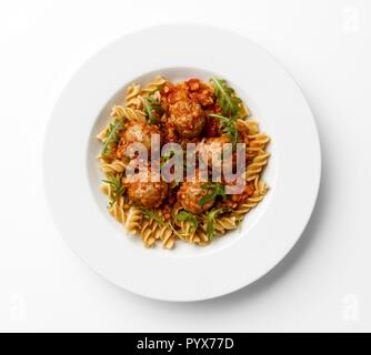 Meatballs in a tomato sause with paste twists with a rocket garnish on a white plate, on a white background. - Stock Photo