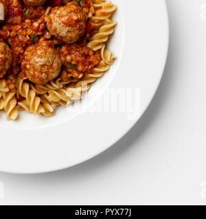Corner of a plate of Meatballs in a tomato sause with paste twists, on a white background. - Stock Photo