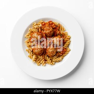 Meatballs in a tomato sause with paste twists on a white plate, on a white background. - Stock Photo