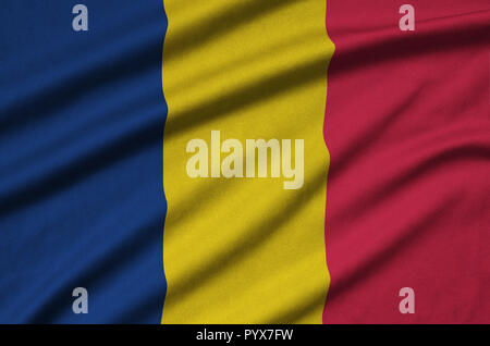 Chad flag  is depicted on a sports cloth fabric with many folds. Sport team waving banner - Stock Photo