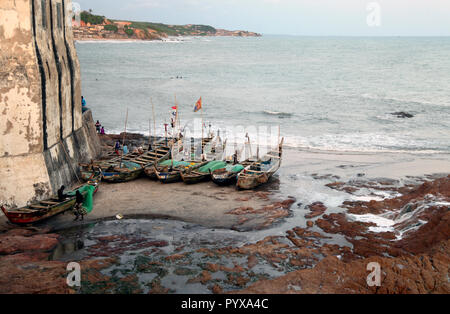 Fishermen and fishing boats at the base of Cape Coast Castle in Cape Coast, Ghana - Stock Photo