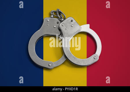 Chad flag  and police handcuffs. The concept of observance of the law in the country and protection from crime. - Stock Photo