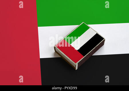United Arab Emirates flag  is pictured on a matchbox that lies on a large flag. - Stock Photo
