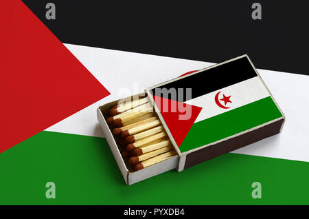 Western Sahara flag  is shown in an open matchbox, which is filled with matches and lies on a large flag. - Stock Photo