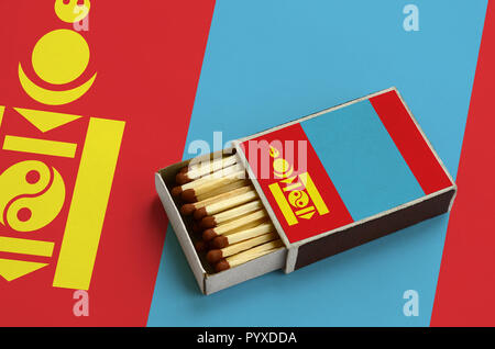 Mongolia flag  is shown in an open matchbox, which is filled with matches and lies on a large flag. - Stock Photo