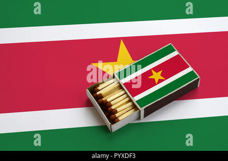 Suriname flag  is shown in an open matchbox, which is filled with matches and lies on a large flag. - Stock Photo