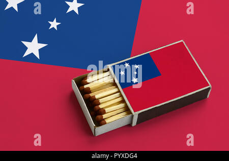 Samoa flag  is shown in an open matchbox, which is filled with matches and lies on a large flag. - Stock Photo