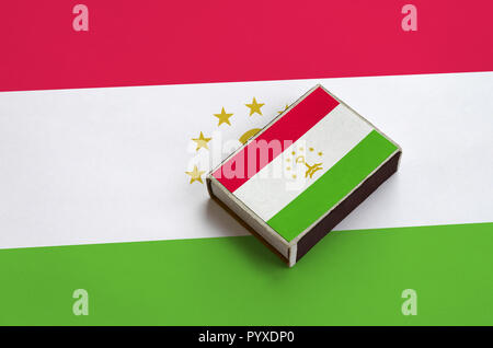 Tajikistan flag  is pictured on a matchbox that lies on a large flag. - Stock Photo