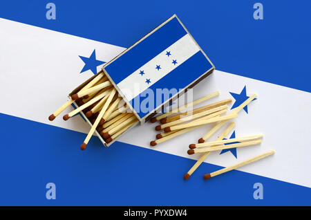Honduras flag  is shown on an open matchbox, from which several matches fall and lies on a large flag. - Stock Photo