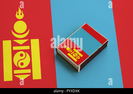 Mongolia flag  is pictured on a matchbox that lies on a large flag. - Stock Photo