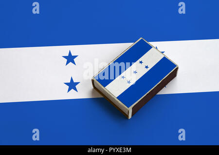 Honduras flag  is pictured on a matchbox that lies on a large flag. - Stock Photo