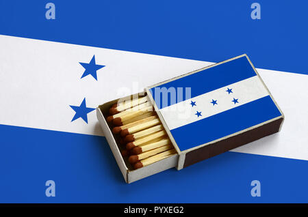 Honduras flag  is shown in an open matchbox, which is filled with matches and lies on a large flag. - Stock Photo