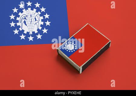 Myanmar flag  is pictured on a matchbox that lies on a large flag. - Stock Photo