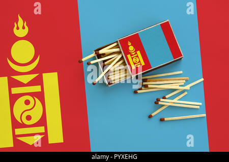 Mongolia flag  is shown on an open matchbox, from which several matches fall and lies on a large flag. - Stock Photo