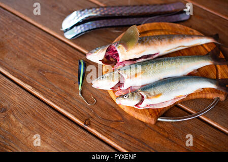 Fresh sea fish catch lies on a cutting Board on a wooden table. Top view copy space - Stock Photo
