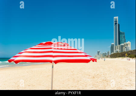 The beautiful white sands, iconic beach umbrella and the Surfers Paradise city skyline in South-east Queensland. - Stock Photo