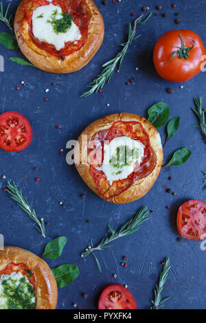 Homemade Mini Pizza with Tomatoes, Cheese and Bacon, Injuries and Spices on Dark Background. - Stock Photo