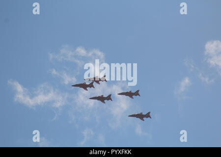 Red Arrows flying in formation through blue skies with fluffy clouds - Stock Photo