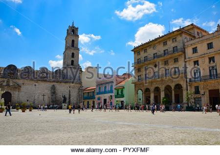 Plaza de San Francisco in Havana, Cuba, church, colonial houses, colorful, blue sky, clouds, sunny, tourists, historic, sightseeing, vacation, old - Stock Photo