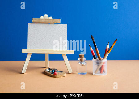 Wooden easel with textured blank paper canvas on blue brown background. Beautiful art class studio interior, watercolor brushes, pencils in a case, water. Artist's advertising poster mockup. - Stock Photo