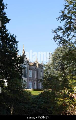 Sheffield Park House through the trees - Stock Photo
