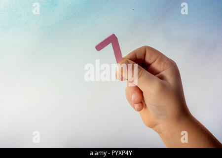 Number 7 seven  made of wood in the hand of a toddler - Stock Photo