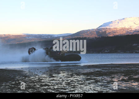 U.S. Marines and Sailors with 24th Marine Expeditionary Unit conduct an amphibious landing from ship to shore, carried on a Landing Craft Air Cushion, during Exercise Trident Juncture 18 in Alvund, Norway, Oct. 29, 2018. Trident Juncture is a multinational NATO exercise that enhances professional relationships and improves overall coordination with Allied and partner nations. (U.S. Marine Corps photo by Sgt. Averi Coppa/Released) - Stock Photo