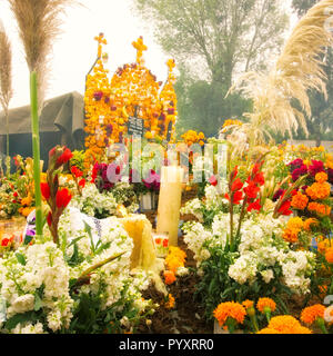 Flowers and candles decorate a tomb on Day of the Dead in Tzintzuntzan, Michoacan, Mexico. - Stock Photo