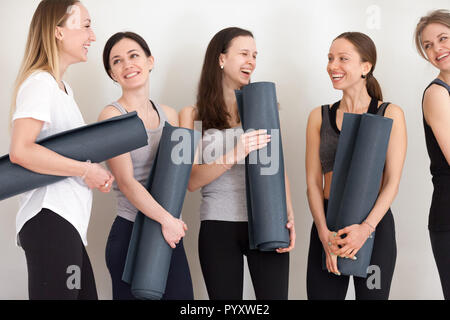 Sportive girls talking holding yoga mats after workout - Stock Photo