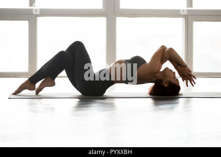 Young sporty yogi woman practicing yoga, doing Matsyasana exercise, Fish pose, working out, wearing sportswear, grey pants, top, indoor full length, a - Stock Photo