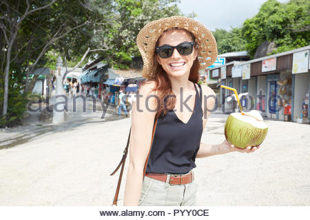 Young woman wearing sunglasses holding coconut drink - Stock Photo