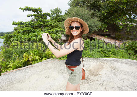 Young woman wearing sunglasses holding camera on rock - Stock Photo