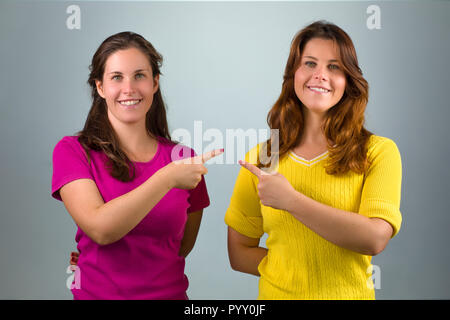 Two Twin Sisters Pointing Each Other - Stock Photo