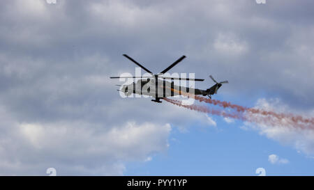 Combat helicopter with red smoke on blue sky with white clouds. View from the bottom. - Stock Photo