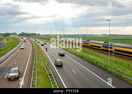 Cars on the A44 highway and a train near the village of Abbenes in the Netherlands. - Stock Photo
