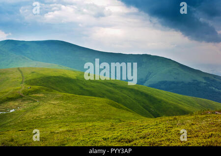 Tiny figures of people hiking on a winding road in the valley among majestic green mountain hills covered in green lush grass. Cloudy day in spring. B - Stock Photo
