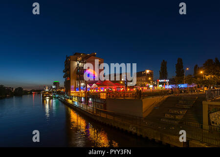 View from the Oberbaum Bridge to a restaurant on the Spree at night, Kreuzberg, Berlin, Germany - Stock Photo