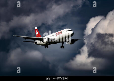 Swiss Airbus A320, in flight in front of dark cloudy sky, Switzerland