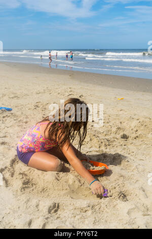 Young Caucasian girl digging playing in sand at Outer Banks North Carolina beach with group of people playing in ocean in the background - Stock Photo