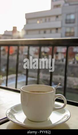 Steaming cup of coffee in the balcony - Stock Photo