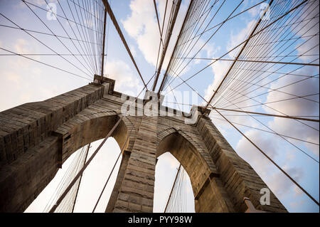 Close-up abstract view of the stone tower arch and steel suspension cables of the Brooklyn Bridge under scenic sunset skies - Stock Photo