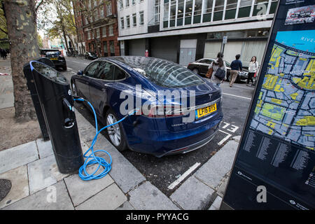 Tesla Model S electric car charging on the street in central London, England, UK - Stock Photo