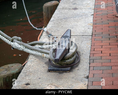 Ropes from a boat tied to a cleat hitch on concrete harbor area - Stock Photo