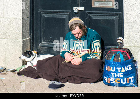 A homeless man and his dog sitting in a doorway. - Stock Photo