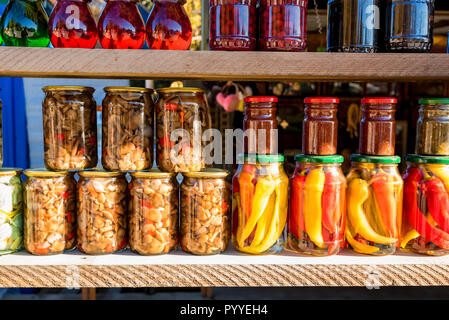 Preserved autumn vegetables and jam in jars - Stock Photo