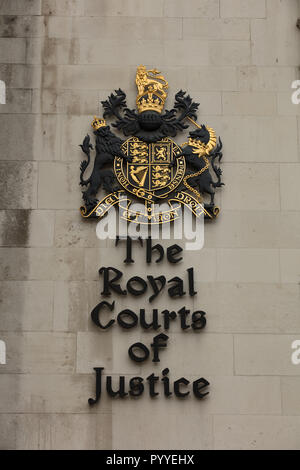 Sign of The Royal Courts of Justice fixed in the outside of the Victorian Gothic style building on the Strand, London, UK, with the Royal Coat of Arms - Stock Photo